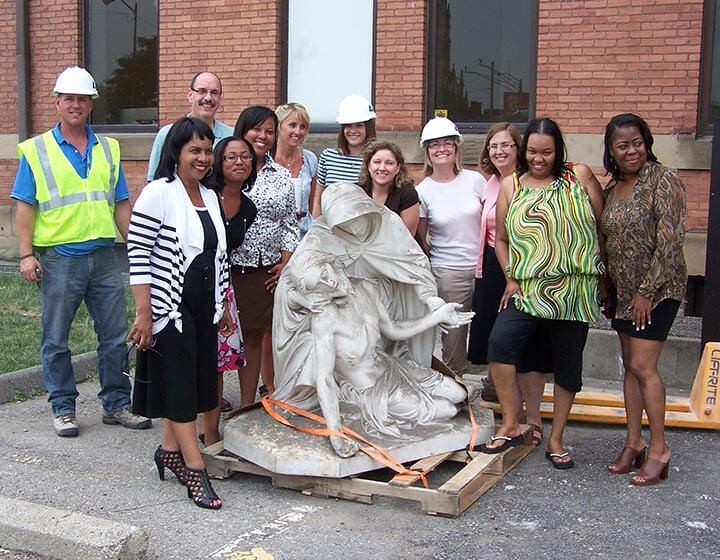 Reclaimed Sculpture of Mary and Jesus surrounded by U of D staff.
