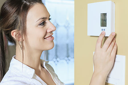 woman setting electronic thermostat